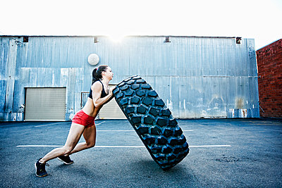 Caucasian woman working out with heavy tire outdoors - p555m1304123 by Peathegee Inc