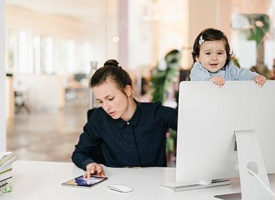 Junge Geschäftsfrau mit Tochter im Büro - p586m1451948 von Kniel Synnatzschke
