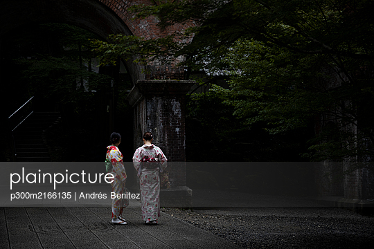 Japan, Kyoto, Rear view of two women wearing kimono  - p300m2166135 by Andrés Benitez