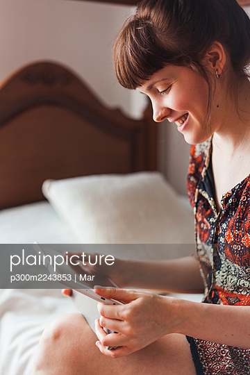 Smiling woman watching video on digital tablet while sitting on bed - p300m2243853 by Mar