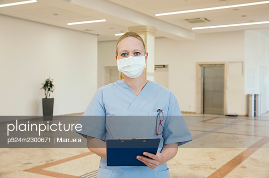 Austria, Vienna, Portrait of nurse in face mask holding clipboard in hospital - p924m2300671 by Manuela