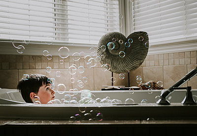 Boy looking at bubbles while taking bath in bathtub - p1166m2001049 by Cavan Images