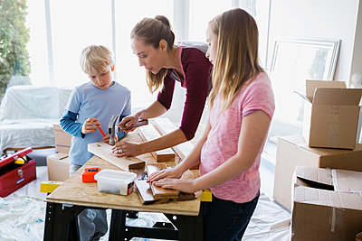 Children watching mother hammer nail into wood trim - p1192m1019843f by Hero Images