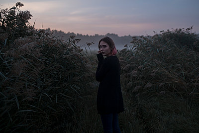 Young woman between bushes at sunset - p1427m2169258 by Vyacheslav Chistyakov