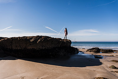 France, Crozon peninsula, teenage girl standing on rock at the beach - p300m1189414 by Uwe Umstätter