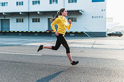 Young woman running on a street - p300m1568507 by Uwe Umstätter