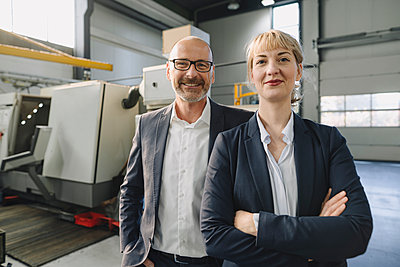 Portrait of confident businessman and businesswoman in a factory - p300m2171115 by Kniel Synnatzschke