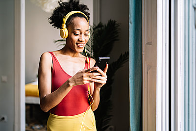 Young woman with headphones using smart phone while standing near window at home - p300m2275325 by COROIMAGE