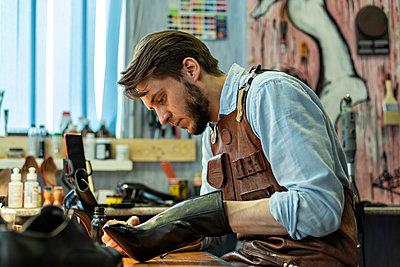 Male craftsperson repairing shoe at workshop - p300m2282564 by Vladimir Godnik