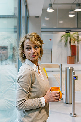 Beautiful female entrepreneur holding coffee mug in coworking office - p300m2282925 by Xavier Lorenzo