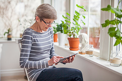 Senior woman using digital tablet - p312m1407446 by Malin Kihlstrom