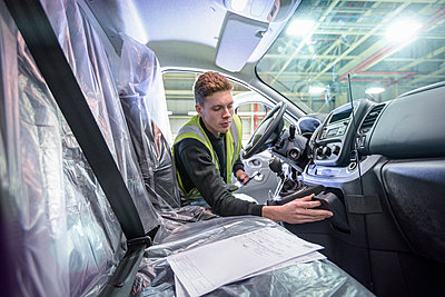 Apprentice vehicle inspector inspecting interior of vehicle in car factory - p429m1408223 by Monty Rakusen
