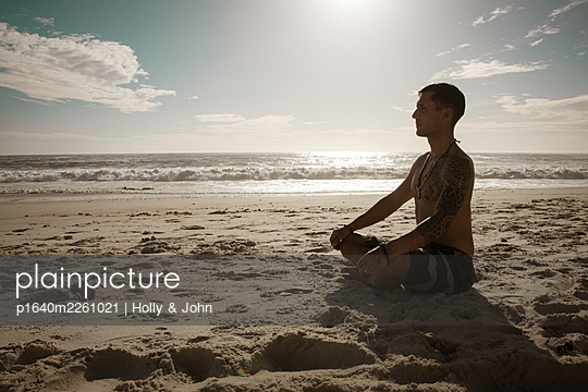 Man practises meditation on the beach at sunset - p1640m2261021 by Holly & John