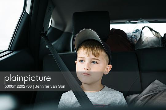 Cute boy looking away while sitting in car - p300m2202736 by Jennifer van Son