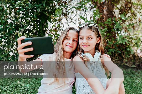 Friends taking selfie while enjoying in garden - p300m2287418 by Eva Blanco