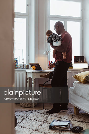 Businessman carrying baby boy while using laptop at home office - p426m2279878 by Maskot