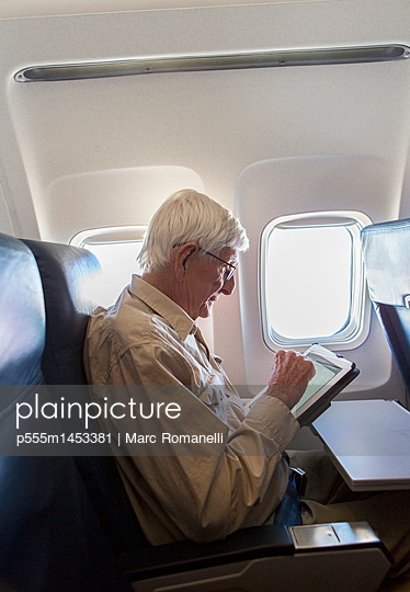 Older Caucasian man using tablet computer on airplane