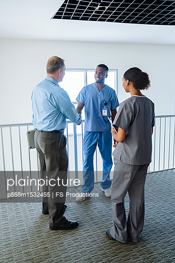 Doctor and nurse shaking hands near railing - p555m1532455 by FS Productions