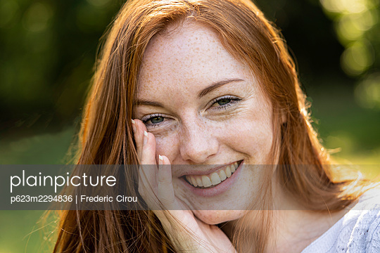 Portrait of smiling young woman in park - p623m2294836 by Frederic Cirou
