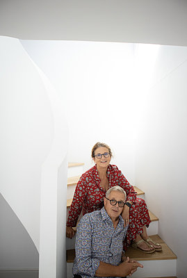 Happy senior couple sitting on stairs - p1640m2254757 by Holly & John