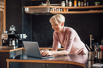Happy businesswoman working on laptop at kitchen counter in home office - p300m2266976 by Robijn Page