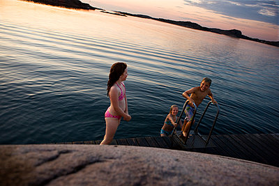 Three children bathing in lake - p972m1088621 by Berno Hjälmrud