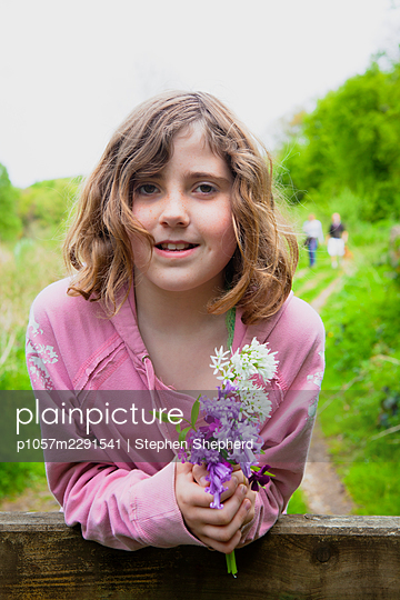 Portrait of a young girl leaning on a wooden country gate with a handful of wild flowers. - p1057m2291541 by Stephen Shepherd