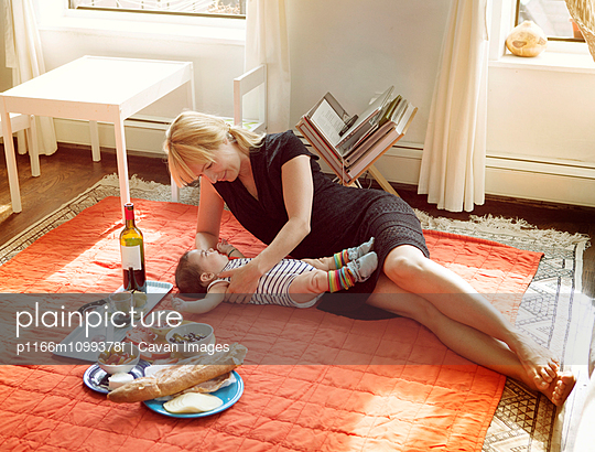 Woman lying on carpet with daughter by food at home - p1166m1099378f by Cavan Images