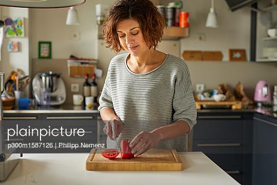 Mature woman cutting tomato in kitchen - p300m1587126 von Philipp Nemenz