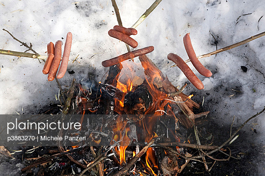 Sausage spears over campfire - p3883270 by Michele Panzeri