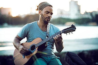 Man playing guitar while sitting at lakeshore during sunset - p1166m1210000 by Cavan Images