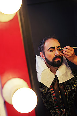 Theater actor having make-up applied in front of a mirror - p1540m2100928 by Marie Tercafs