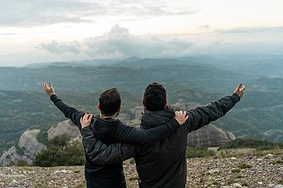 friends standing on mountain peak with arms around, enjoying he view - p300m2078746 von VITTA GALLERY