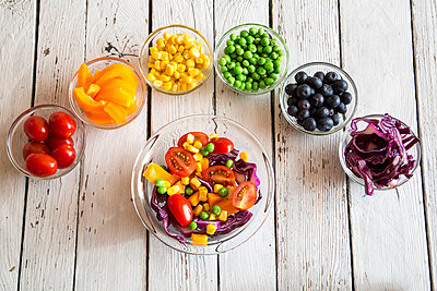 Mixed salad and glass bowls with different raw vegetables  rainbow-coloured arranged on white wood - p300m978882f by Sandra Roesch