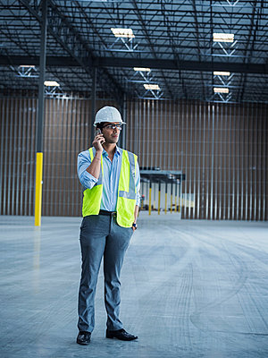 Indian worker talking on cell phone in empty warehouse - p555m1305144 by Erik Isakson