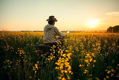 Mari man riding motorcycle in field of flowers - p555m1420948 by Aliyev Alexei Sergeevich