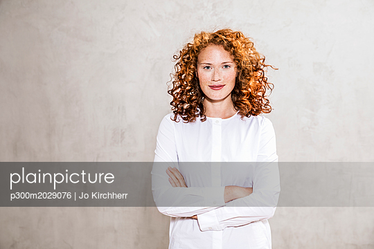 Portrait of redheaded young woman with arms crossed - p300m2029076 by Jo Kirchherr