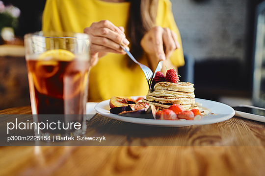 Midsection of young female eating pancake while sitting at table in cafe - p300m2225154 by Bartek Szewczyk