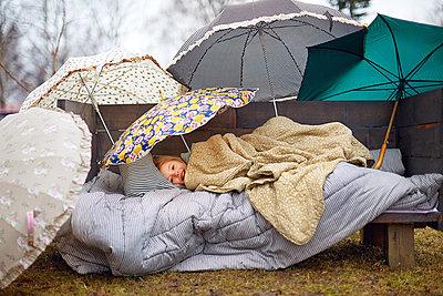 Girl lying on a bench under umbrellas - p1239m2272790 by Krista Keltanen