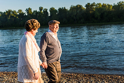 Happy senior couple walking hand in hand at riverside - p300m1460381 by Uwe Umstätter