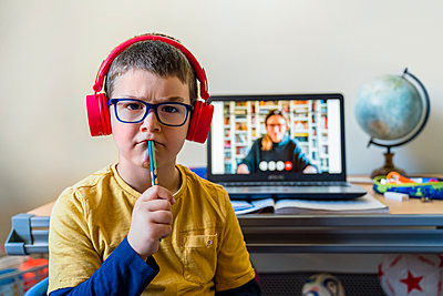 Thoughtful boy sitting against laptop during video call at home - p300m2198681 by Giorgio Magini