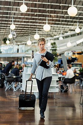 Businessman using smart phone while walking at airport - p426m1114681f by Maskot