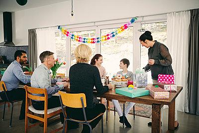 Multi-generation family enjoying food at birthday party - p426m1580227 by Maskot