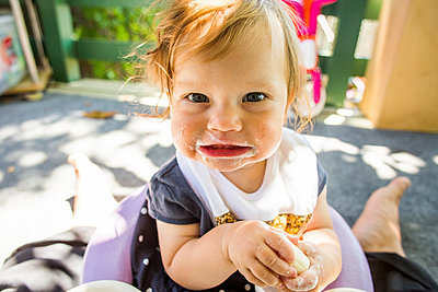 Caucasian baby girl eating on patio - p555m1411247 by Adam Hester
