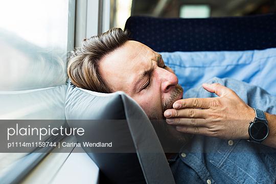 Mann gähnt im Zug - p1114m1159744 von Carina Wendland