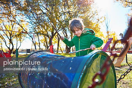 Boy drumming on cask on playground - p300m2069351 by Stefan Schütz