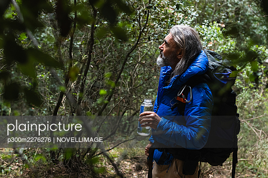 Senior male explorer looking at plants while holding water bottle in forest - p300m2276276 by NOVELLIMAGE