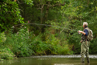 Man casting fly fishing pole at remote green river - p1023m2262056 by Martin Barraud