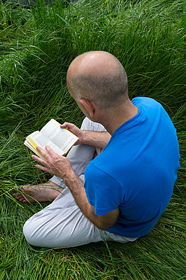Man in blue t-shirt reading a book in the meadow - p1096m1144566 by Rajkumar Singh