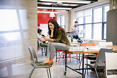 Businesswoman using smart phone in coworking space - p1192m2094745 by Hero Images